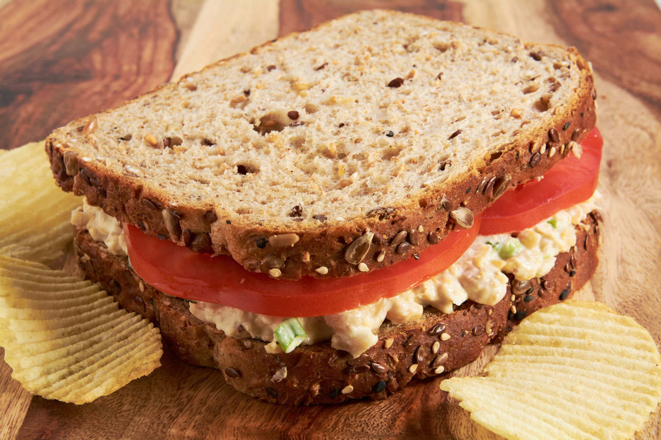 A sandwich made with whole grain bread, tomato slices and chickpea salad on a cutting board.