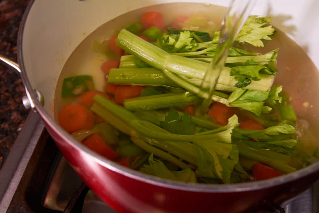 Adding water to a pot of veggies