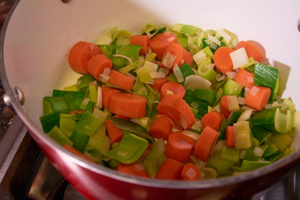 Pot with leeks and carrots being cooked