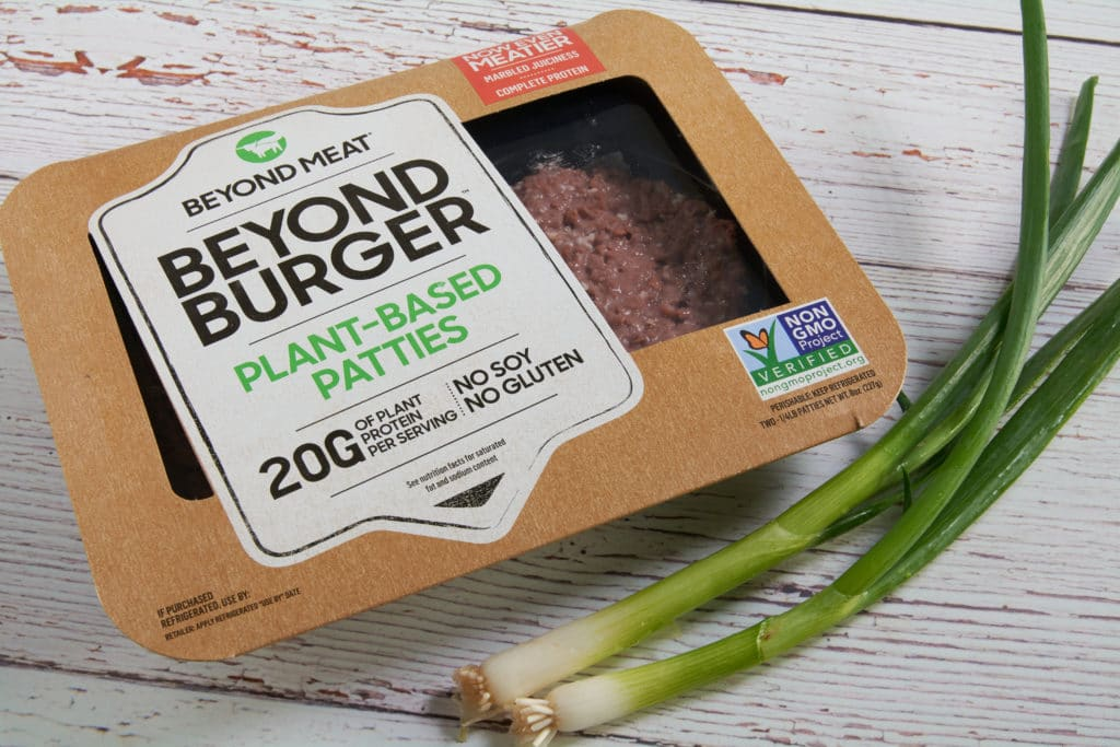 Package of beyond burgers and green onions on a table