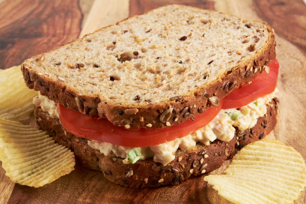 A sandwich made with whole grain bread, tomatoes and chickpea salad sitting on a cutting board.