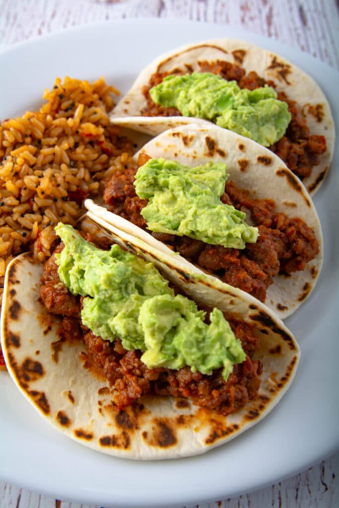 Three tacos with rice on a plate