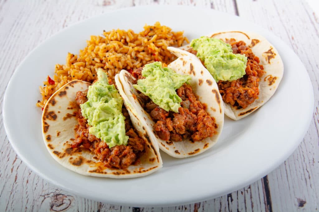 Three tacos with rice on a plate.