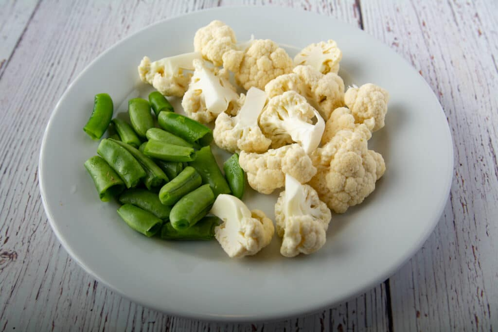 Prepared raw cauliflower and green beans in a small bowl