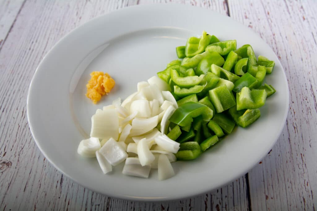 Prepared raw garlic, onion and green bell pepper on a plate.