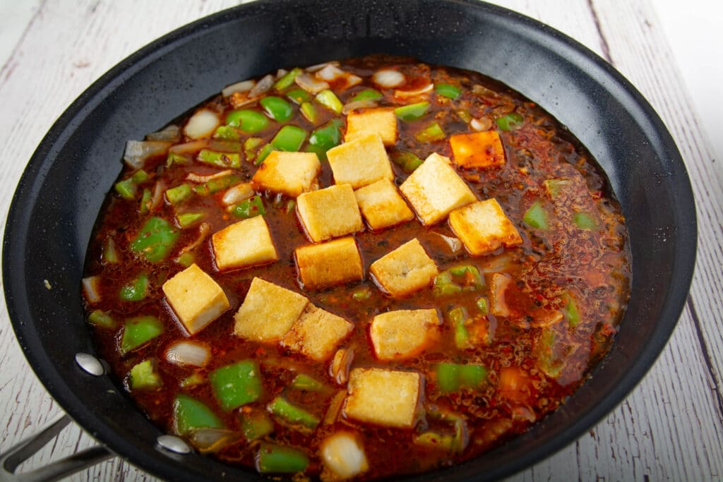 Cooked ingredients with sauce in a pan.