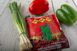 Package of bean paste, bell peppers and green onion on a table