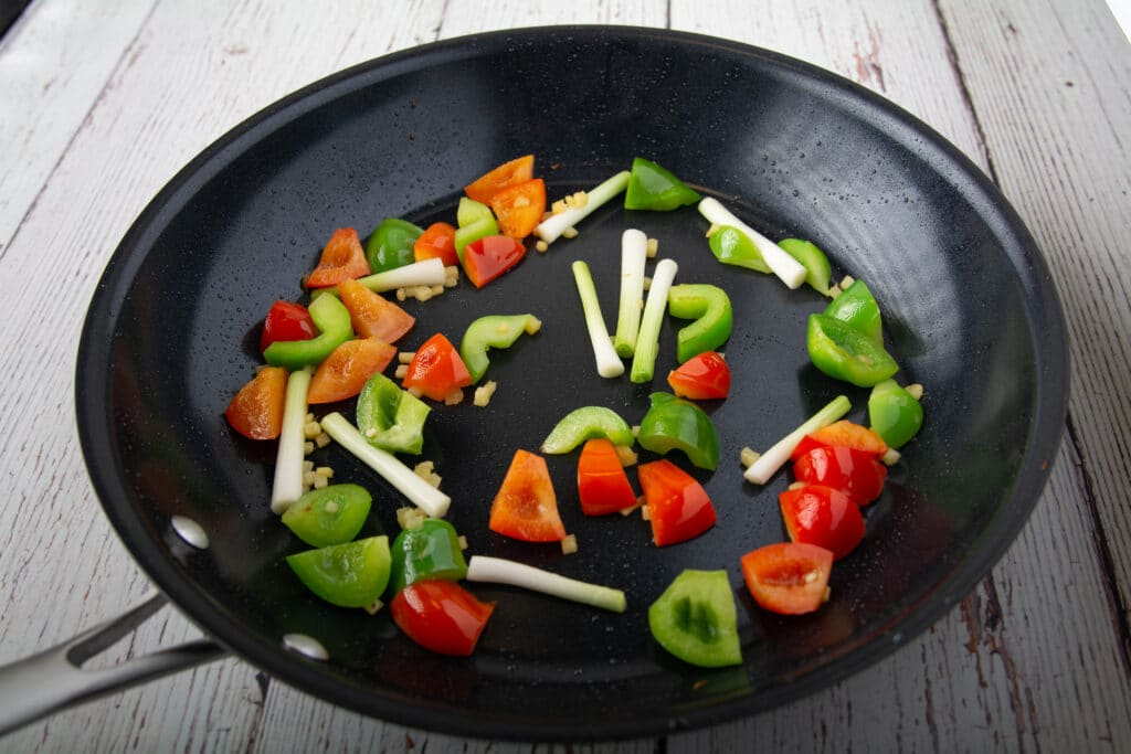 Cooked bell peppers and green onions in a pan