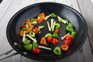 Bell peppers, green onion, garlic and ginger in a pan on a table.