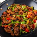 Seitan and vegetables in a spicy sauce in a pan.