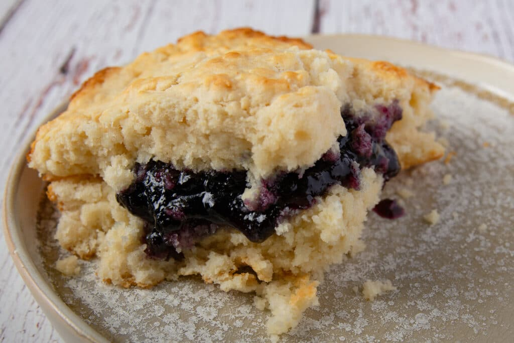 Vegan biscuit with blackberry jelly on a plate.