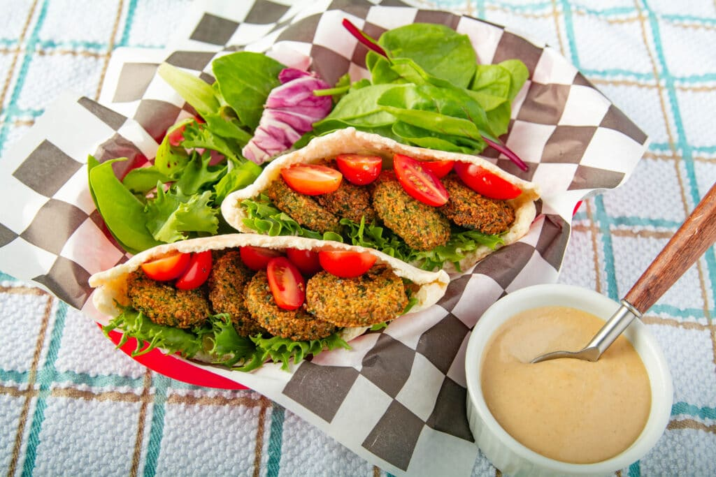Falafel sandwich in a basket with sauce on the side