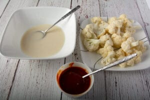 Bowl with the batter, prepared cauliflower and a bowl of sauce.