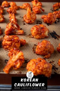 Oven baked cauliflower wings in a spicy Korean sauce on a baking pan fresh out of the oven. This is a pin for Pinterest