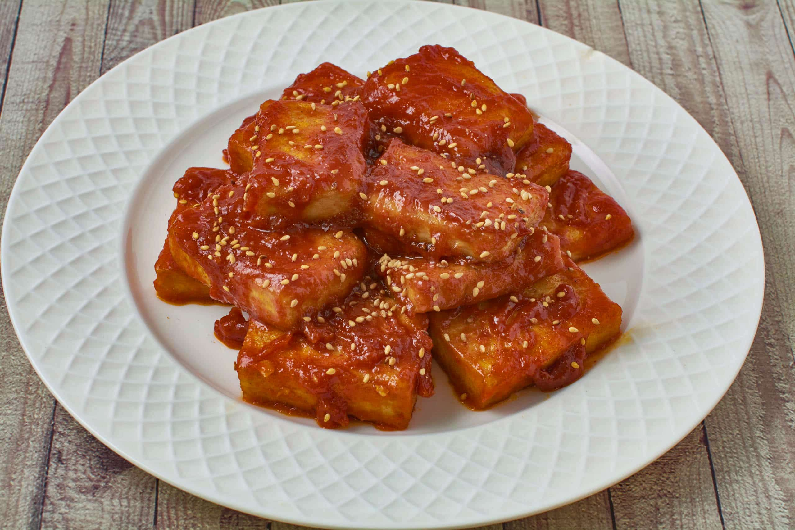 Fried tofu in a spicy sauce on a plate