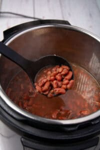 A ladle dipping red beans from the Instant Pot