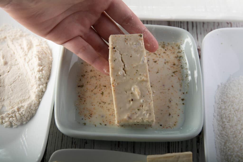 Second step of dredging tofu, showing the tofu with soy milk.