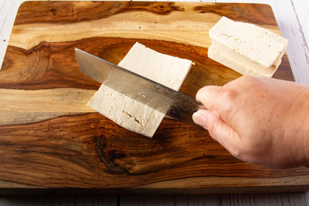 Using a knife to cut tofu into six portions