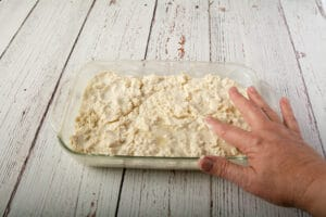 A hand smoothing the top of the vegan biscuit dough