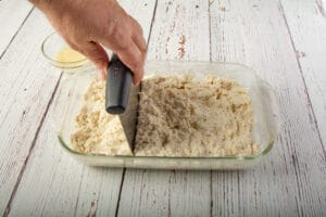 A hand using a bench scraper to portion out the dough
