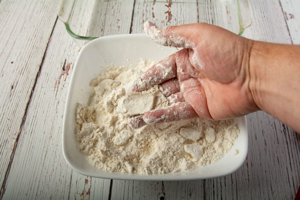 A hand showing how to crumble the vegan butter into the flour.