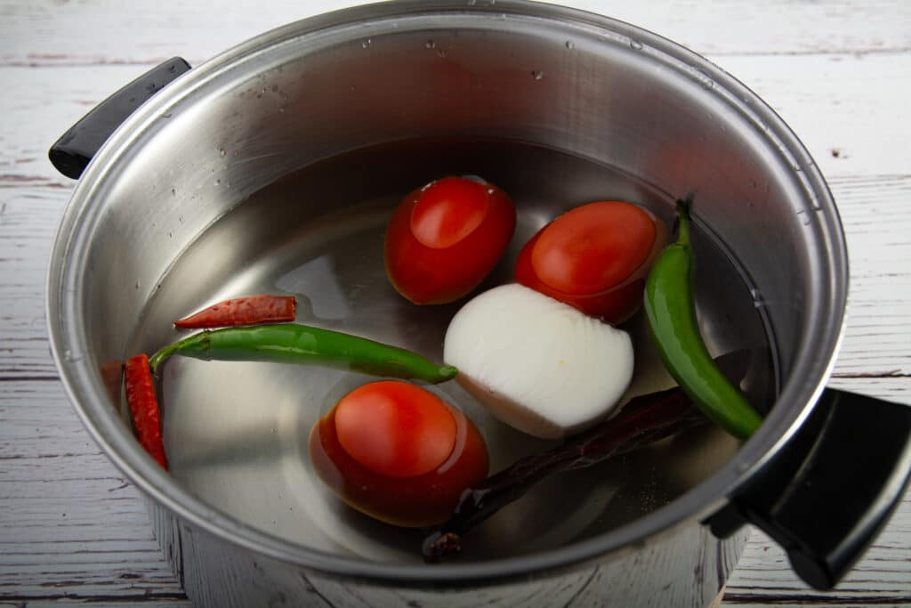Pot with water covering salsa ingredients