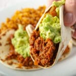 Close up shot of a taco topped with guacamole being held. With more tacos in the background on a plate.