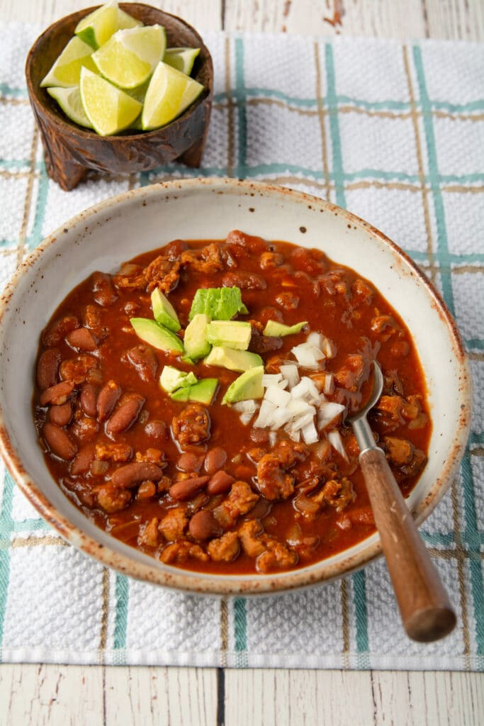 A bowl of homemade vegan chili with a spoon and topped with avocado and onions.