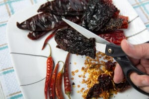 Dried chilis on a plate. Using scissors to cut one on the chilis