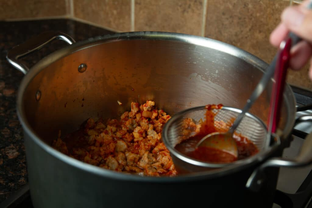 A strainer over the pot of chili with a spoon straining out bits of chili seeds and skin.