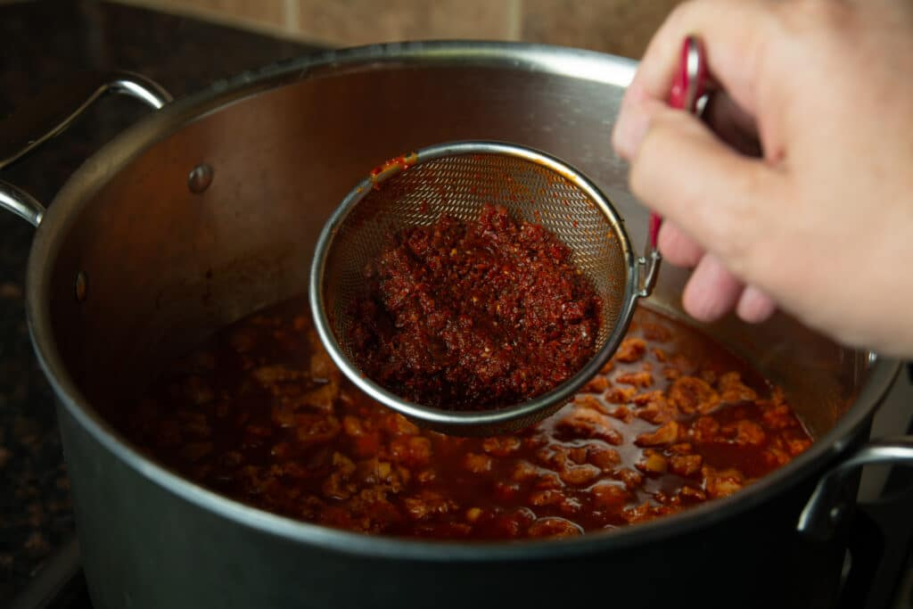 A strainer over the pot of chili with all of the left over bits of chili seeds and skin.