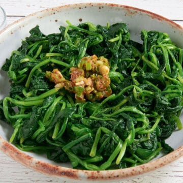 Blanched spinach with seasoning paste in a bowl.