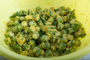 Okra in a bowl with batter ready to fry