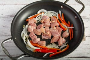 Raw chicken in a pan with onions and bell peppers