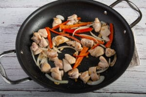 Browned chicken in a pan with onions and bell peppers