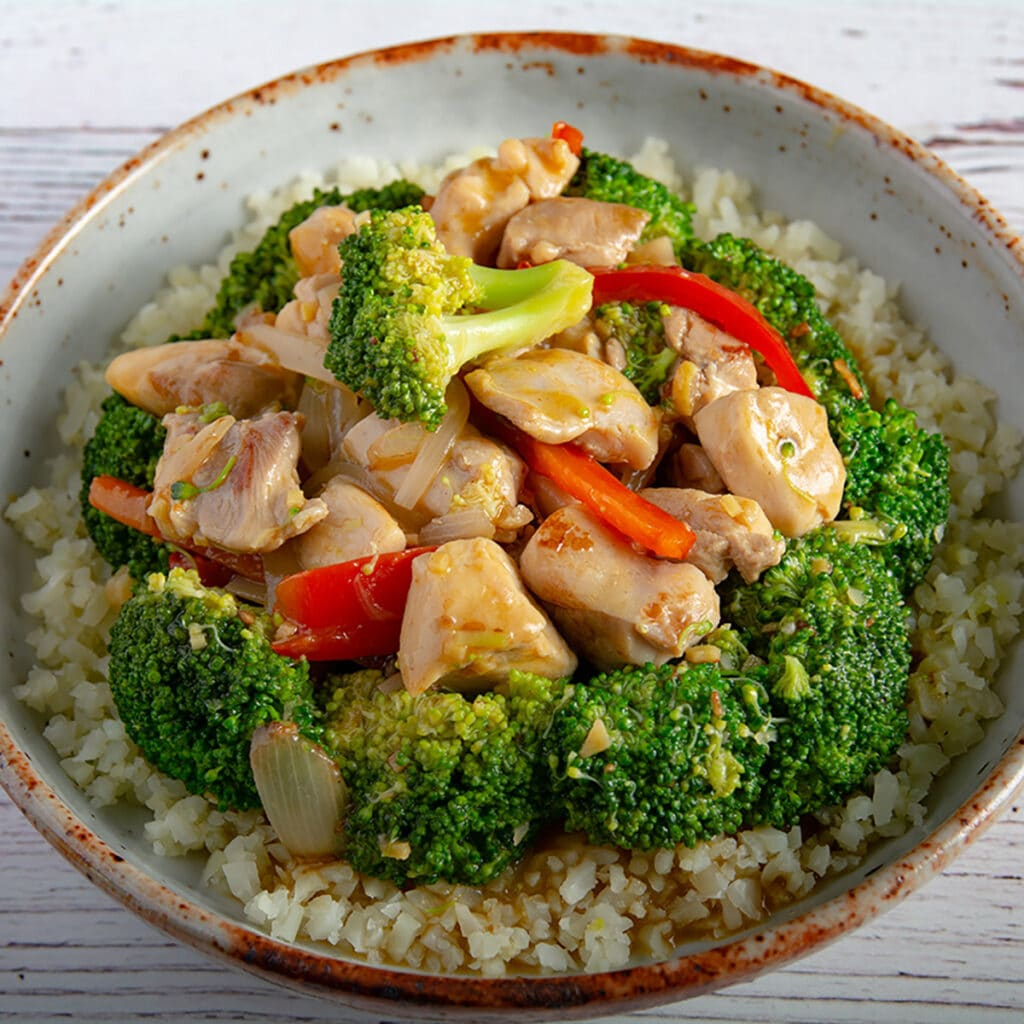 Finished chicken and broccoli in a bowl on a table.