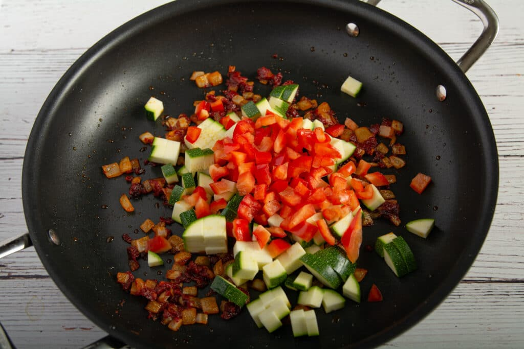 Cooked onions, garlic and tomato paste with raw zucchini and red peppers in a pan