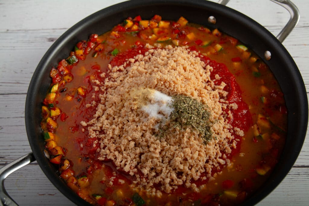 Cooked veggies with tomato sauce, TVP and seasoning in a pan