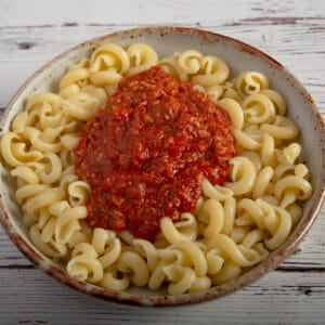 A bowl to pasta topped with sauce