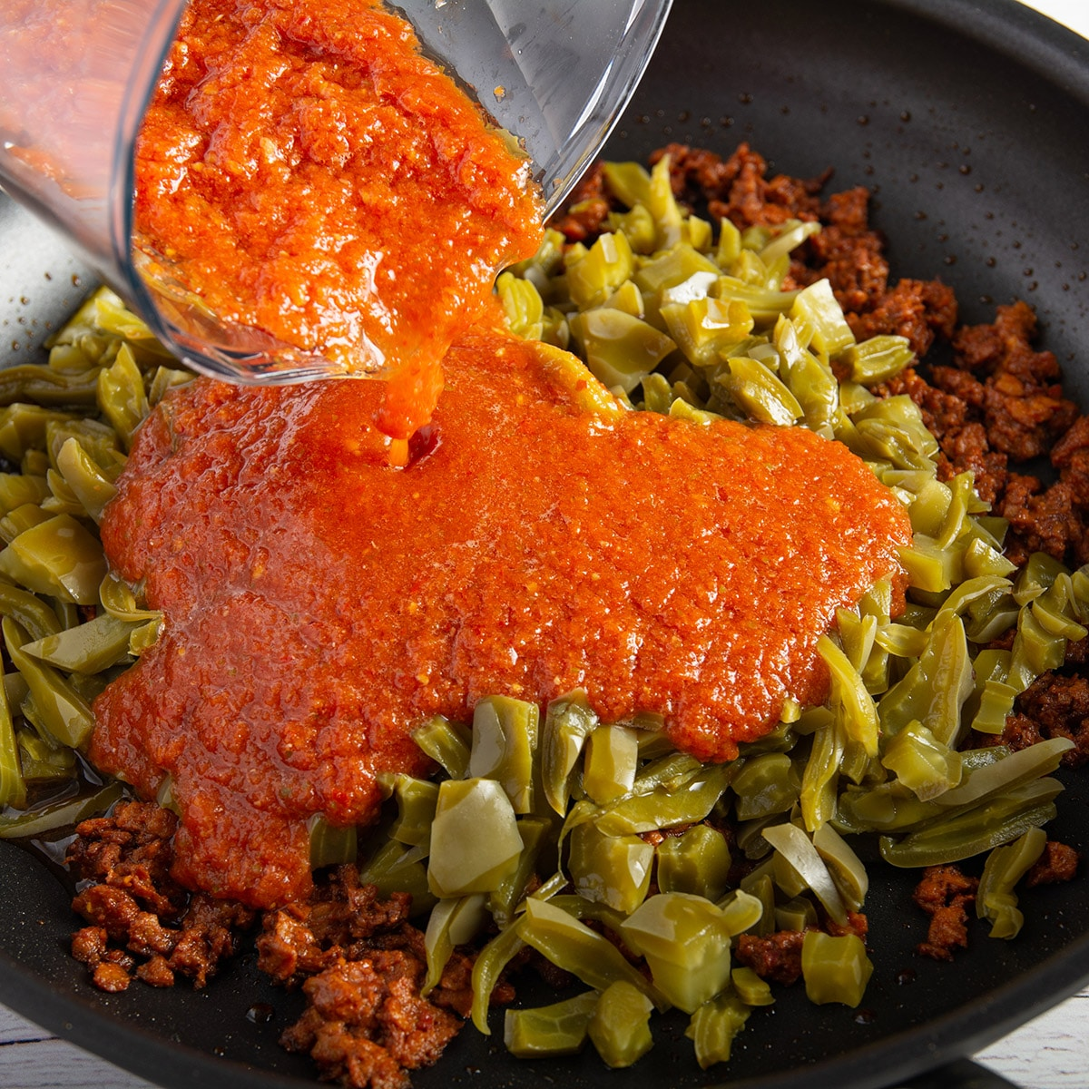 Pouring salsa into a pan with the chorizo and nopales