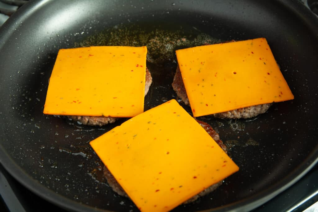 Burger patties in a pan topped with vegan cheese