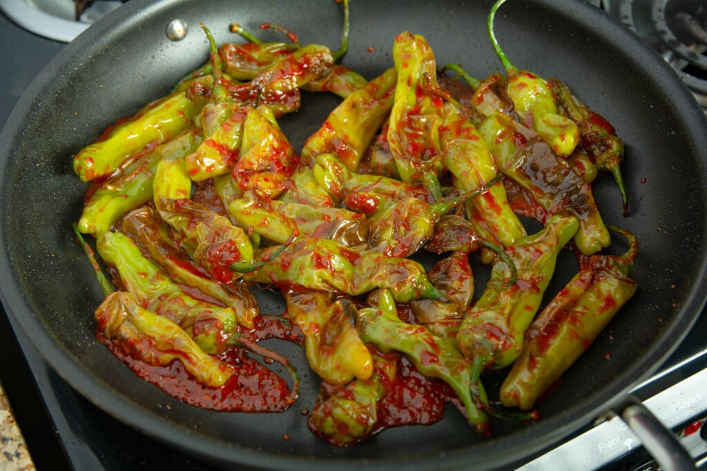 Fried peppers in a pan with spicy sauce