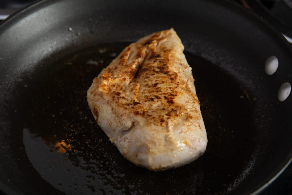 Chicken breast in a pan with the top side seared.