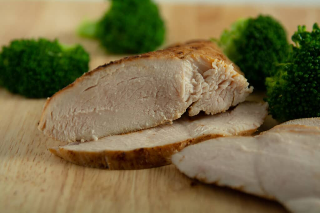Sliced chicken breast on a cutting with some broccoli