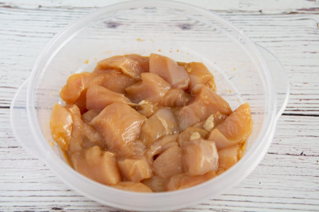 Raw chicken marinating in a bowl