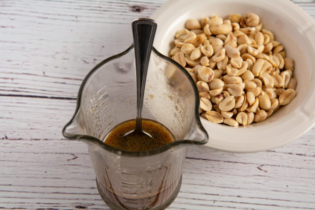 Sauce in a jar and peanuts in a bowl