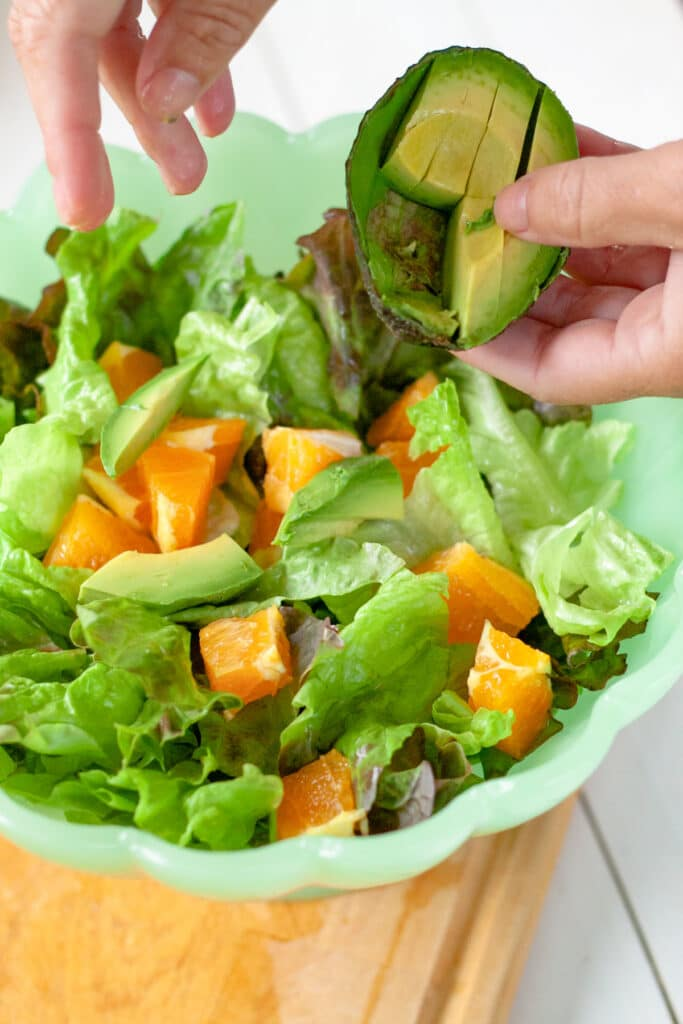 A bowl of salad with a hand sprinkling on chunks of avocado