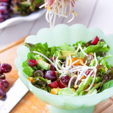 A bowl of salad with a hand sprinkling on bean sprouts.