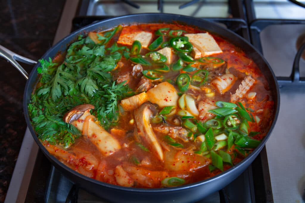 Spicy fish stew cooking on a stove.