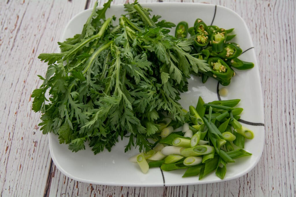 ssuk-gat (crown daisy), green peppers and green onion on a plate.